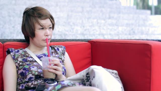 vídeos y material grabado en eventos de stock de ms woman drinking coffee outside / hong kong, china - sólo mujeres jóvenes