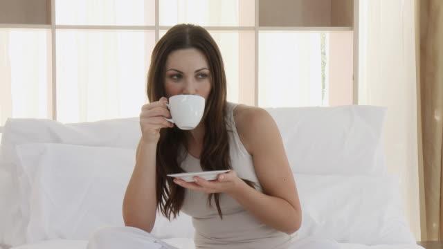 vídeos de stock e filmes b-roll de ms woman drinking coffee, sitting on bed / cape town, western cape, south africa - olhar de lado