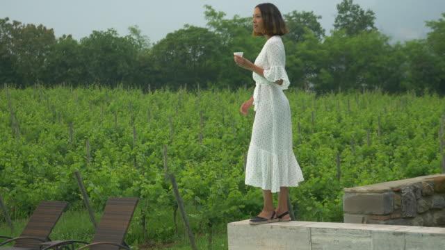 vídeos y material grabado en eventos de stock de a woman drinking coffee traveling at a luxury resort in italy, europe. - slow motion - viña