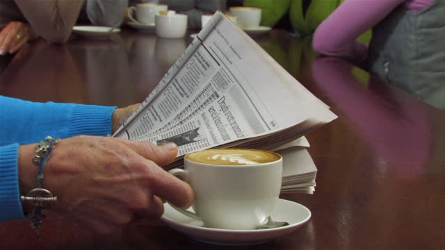vídeos de stock e filmes b-roll de ms woman drinking coffee while reading newspaper, women in background / cape town, western cape, south africa - jornal