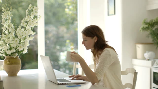 Woman drinking coffee while using laptop in kitchen at home.