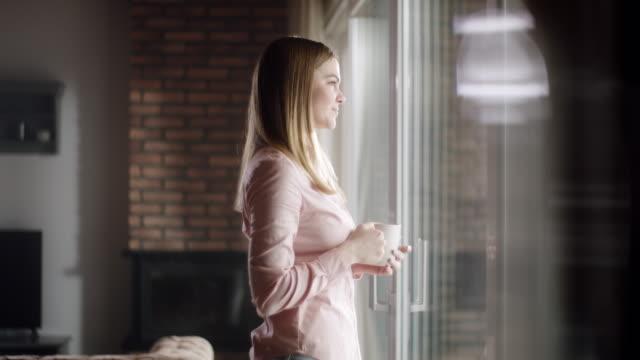 frau trinkt ersten kaffee bei ihr zu hause - gemütlich stock-videos und b-roll-filmmaterial