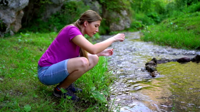 woman drinking fresh nature water from river - named wilderness area stock videos & royalty-free footage