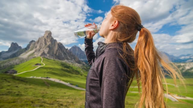 woman drinking from a reusable water bottle, looking at mountains - reusable stock videos & royalty-free footage