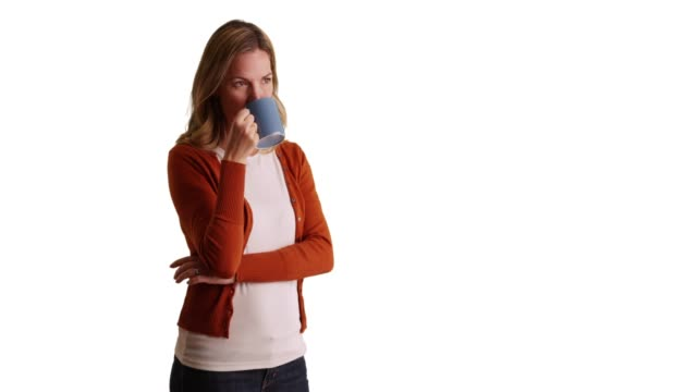 woman drinking from coffee mug in studio with copyspace, looking off camera - coffee drink stock videos & royalty-free footage
