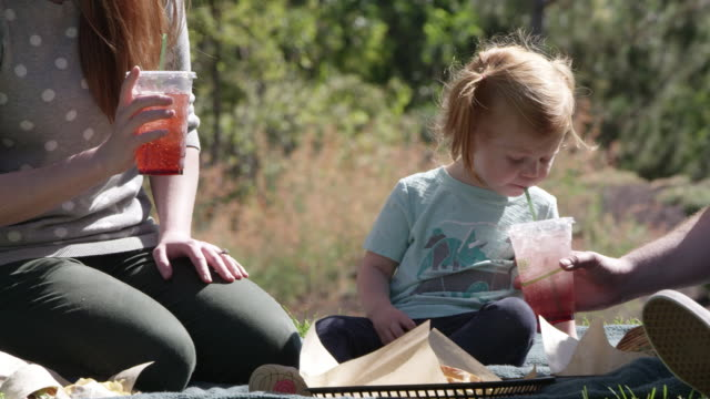 woman drinking from straw as daughter blows into straw - paglia video stock e b–roll