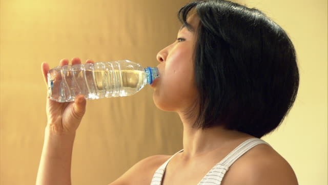 cu woman drinking from water bottle after exercising in yoga studio/ new york, ny - 35 39 jahre stock-videos und b-roll-filmmaterial