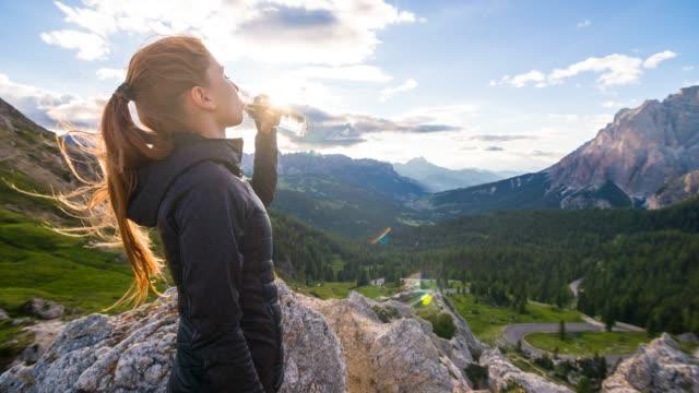 Frau trinkt aus Wasserflasche auf einem Berg mit Blick auf ein Tal bei Sonnenuntergang