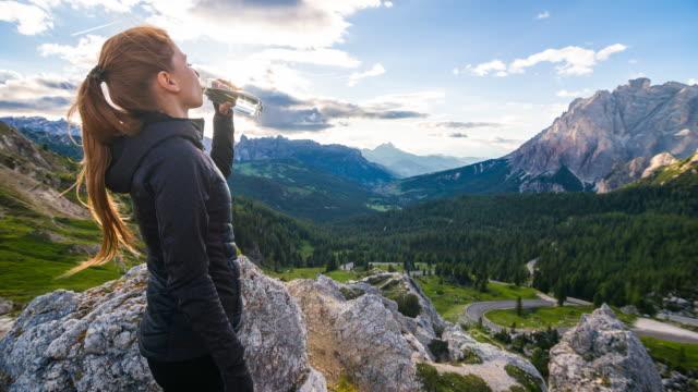 vídeos y material grabado en eventos de stock de mujer bebiendo de una botella de agua en la cima de una montaña con vistas a un valle al atardecer - punta descripción física