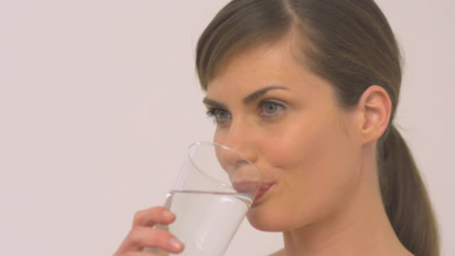 cu slo mo woman drinking glass of water / london, greater london, united kingdom  - einzelne frau über 30 stock-videos und b-roll-filmmaterial
