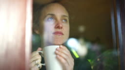 Woman drinking hot beverage looks out of window from inside her apartment