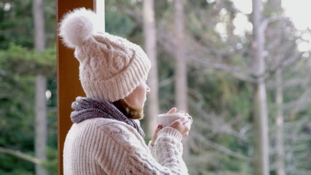 4k woman drinking hot chocolate on winter patio in forest, real time - woolly hat stock videos and b-roll footage