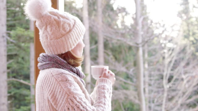 4K Woman drinking hot, steaming tea on winter patio, slow motion