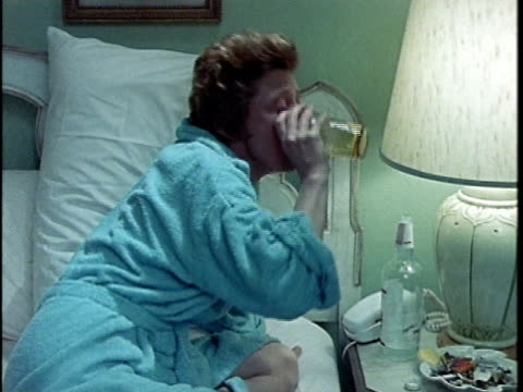 stockvideo's en b-roll-footage met 1971 ms woman drinking in bed, los angeles, california, usa, audio  - alcoholisme