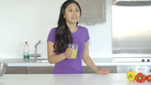 woman drinking juice - オレンジピーマン点の映像素材/bロール
