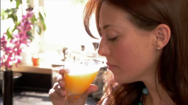 woman drinking orange juice at breakfast / eating fresh fruit and granola - orange juice stock videos and b-roll footage