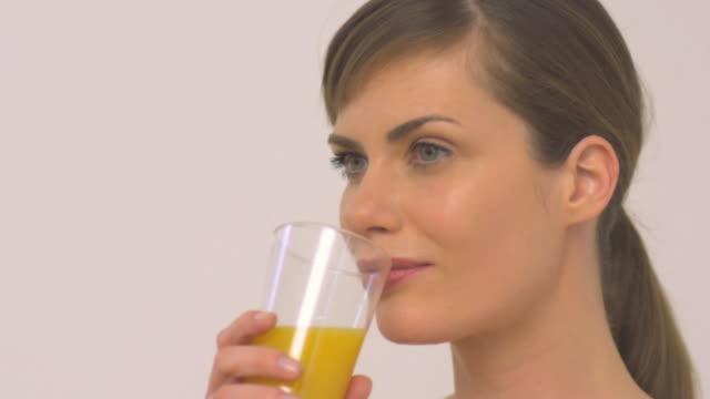 CU SLO MO Woman drinking orange juice / London, Greater London, United Kingdom