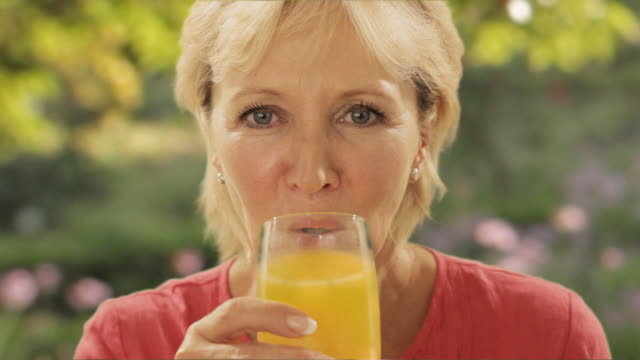 woman drinking orange juice with garden background - orange juice stock videos and b-roll footage