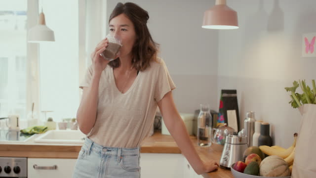 woman drinking smoothie in kitchen at home - vergnügen stock-videos und b-roll-filmmaterial