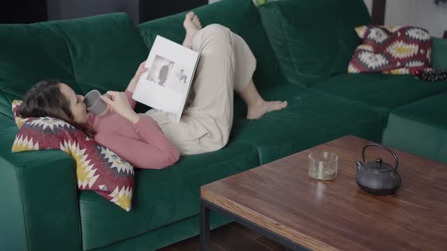 woman drinking tea and reading magazine at home - magazine publication stock videos & royalty-free footage