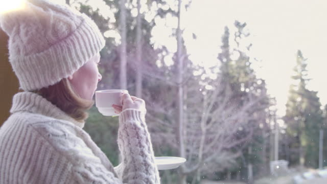 4K Woman drinking tea and watching snow falling in forest, real time
