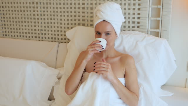 woman drinking tea in bed - wrapped in a towel stock videos & royalty-free footage