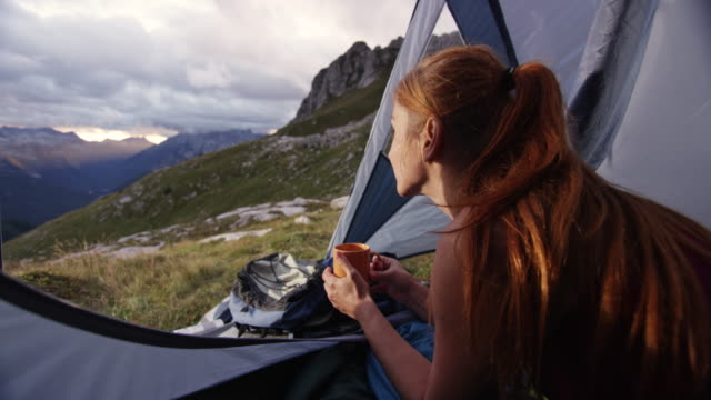 woman drinking tea in the tent high in the mountains and admiring the view - tent stock videos and b-roll footage