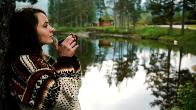 Vrouw het drinken van thee in de buurt van het meer in bos in Noorwegen