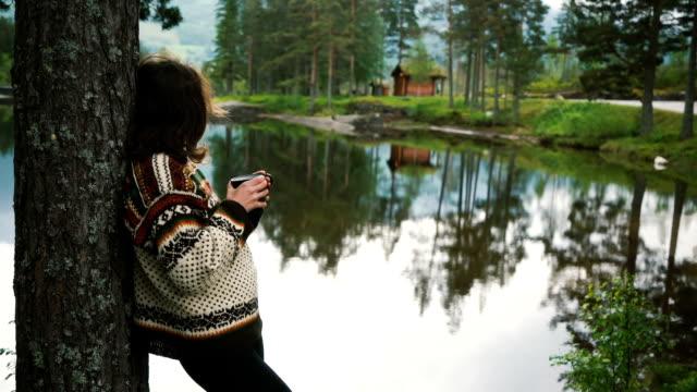 Frau trinkt Tee am See im Wald in Norwegen