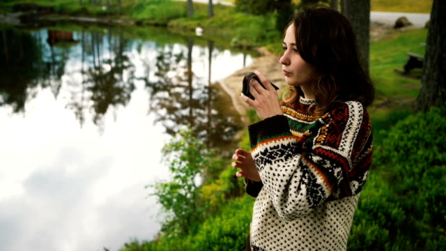 Woman drinking tea near the lake in forest in Norway