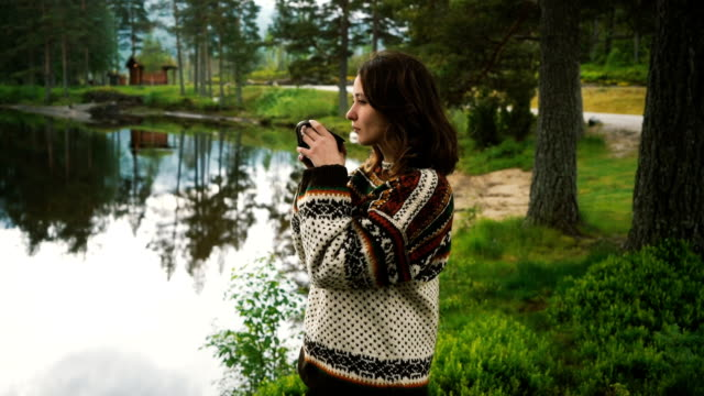 woman drinking tea near the lake in forest in norway - fjord stock videos & royalty-free footage