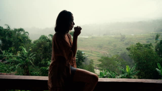 woman drinking tea on balcony with view  on rice fields - hot drink stock videos and b-roll footage