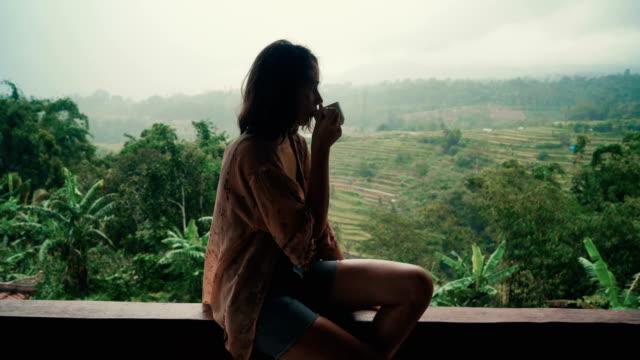 stockvideo's en b-roll-footage met vrouw het drinken van thee op balkon met uitzicht op de rijstvelden - warme dranken