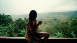 Woman drinking tea on balcony with view  on rice fields