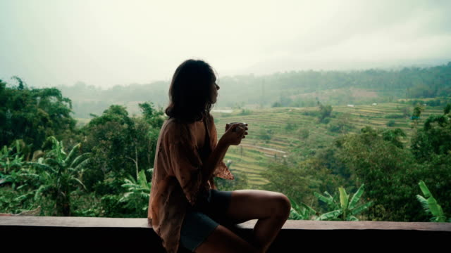 woman drinking tea on balcony with view  on rice fields - piacere video stock e b–roll