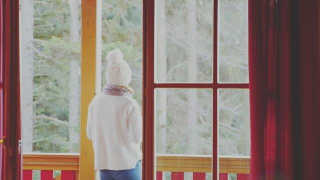 4K Woman drinking tea on winter cabin balcony, real time