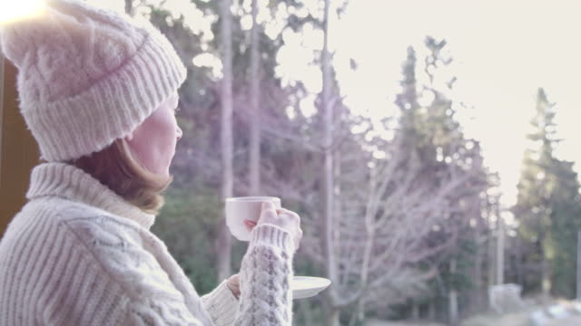 4K Woman drinking tea on winter patio in forest, real time