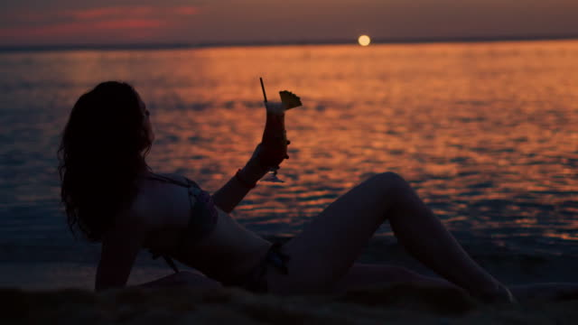 woman drinking tropical drink on beach at sunset - tropical drink stock videos & royalty-free footage