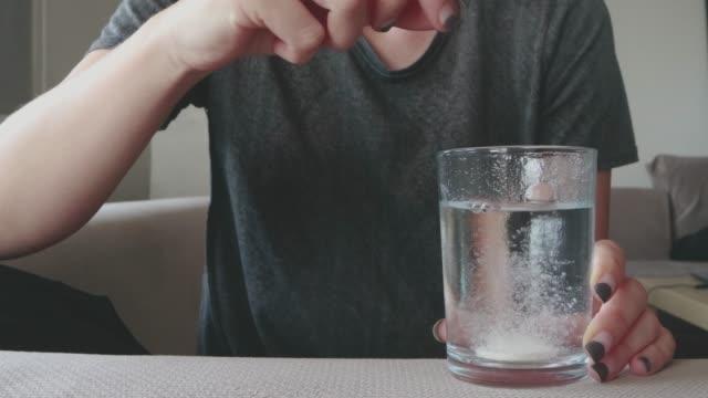 vidéos et rushes de une femme buvant des vitamines pour se protéger des virus - dissolving