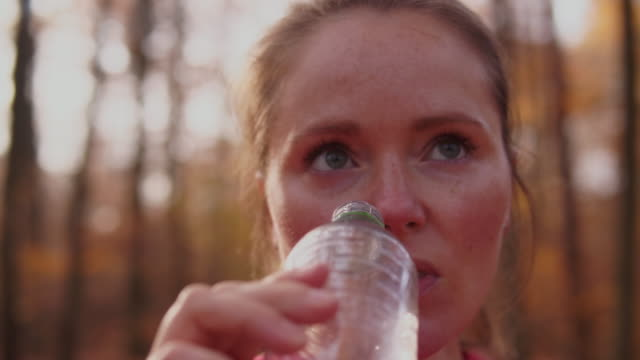 woman drinking water after jogging. - one mid adult woman only stock videos & royalty-free footage