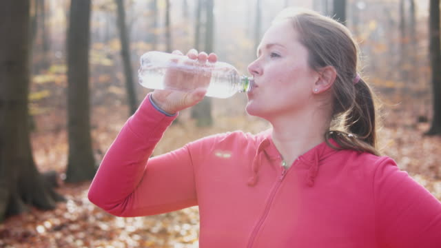woman drinking water after running. - one mid adult woman only stock videos & royalty-free footage