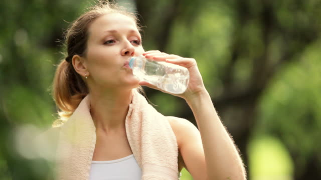 stockvideo's en b-roll-footage met woman drinking water after sport activities - drinkwater