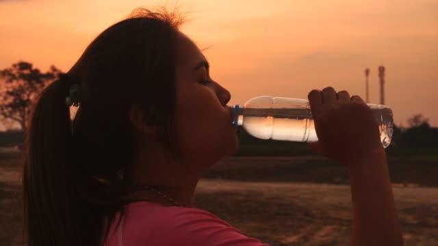stockvideo's en b-roll-footage met het drinkwater van de vrouw bij zonsondergang - gymbroek