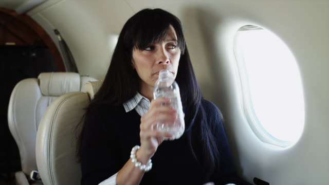 ms woman drinking water from bottle in airplane / spanish fork, utah, usa - bottiglia d'acqua video stock e b–roll