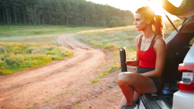 woman drinking water from bottle while sitting at car trunk after trail run - bottle stock videos & royalty-free footage