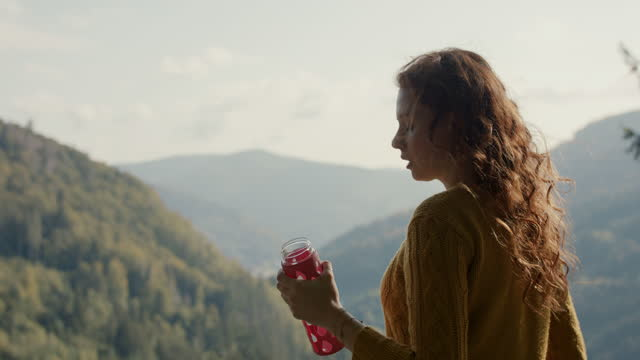 woman drinking water from reusable bottle in front of spectacular scenery - bottle stock videos & royalty-free footage