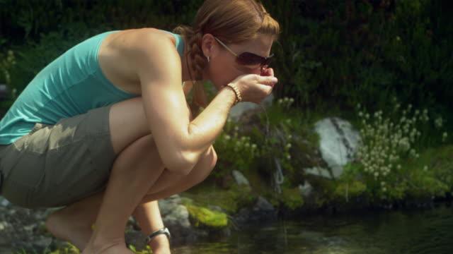 ms tu woman drinking water from stream, garibaldi provincial park, squamish, british columbia, canada - garibaldi park stock videos & royalty-free footage