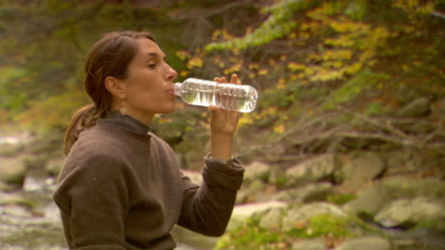 vídeos y material grabado en eventos de stock de cu, woman drinking water in forest, autumn, phoenicia, new york, usa - agua purificada