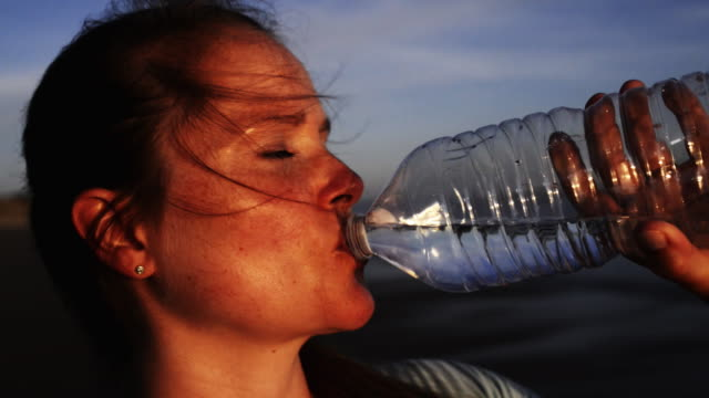 Woman drinking water in sunlight.