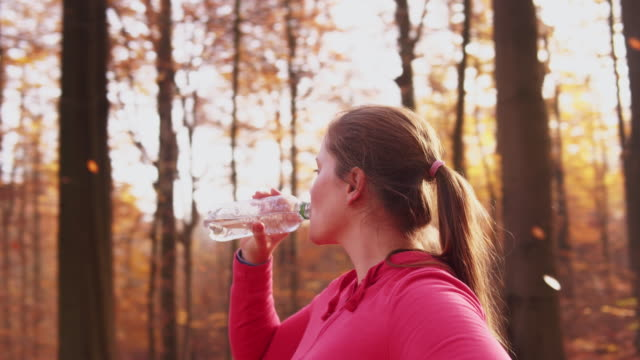 woman drinking water outdoor. - one mid adult woman only stock videos & royalty-free footage
